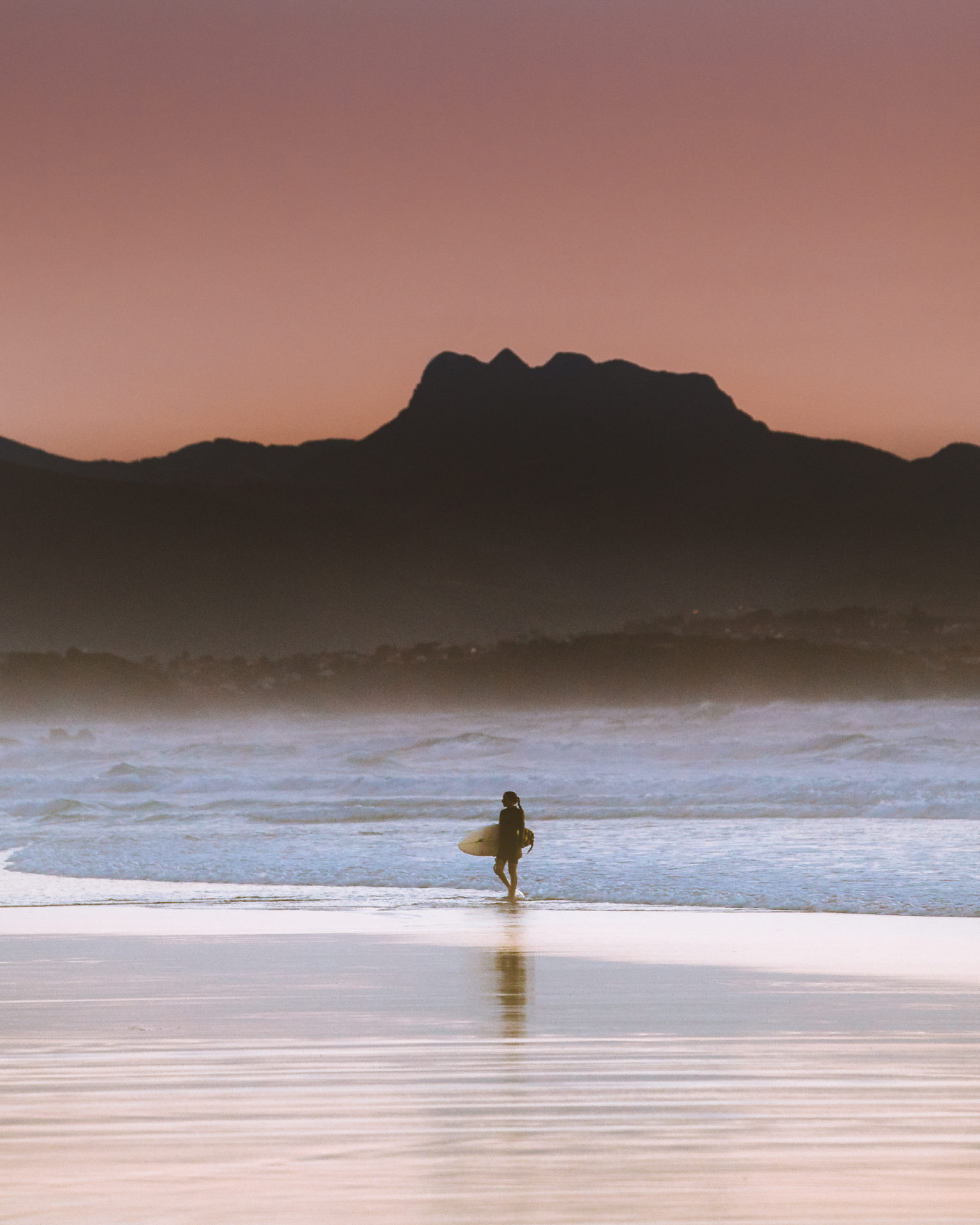 surfeur sur la plage au coucher de soleil