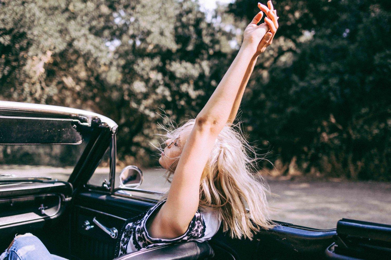 Jeune femme levant les bras dans une voiture