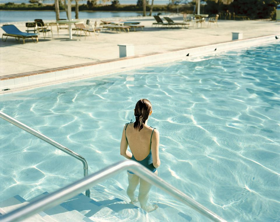 Jeune femme dans une piscine avec des transats en arrière-plan