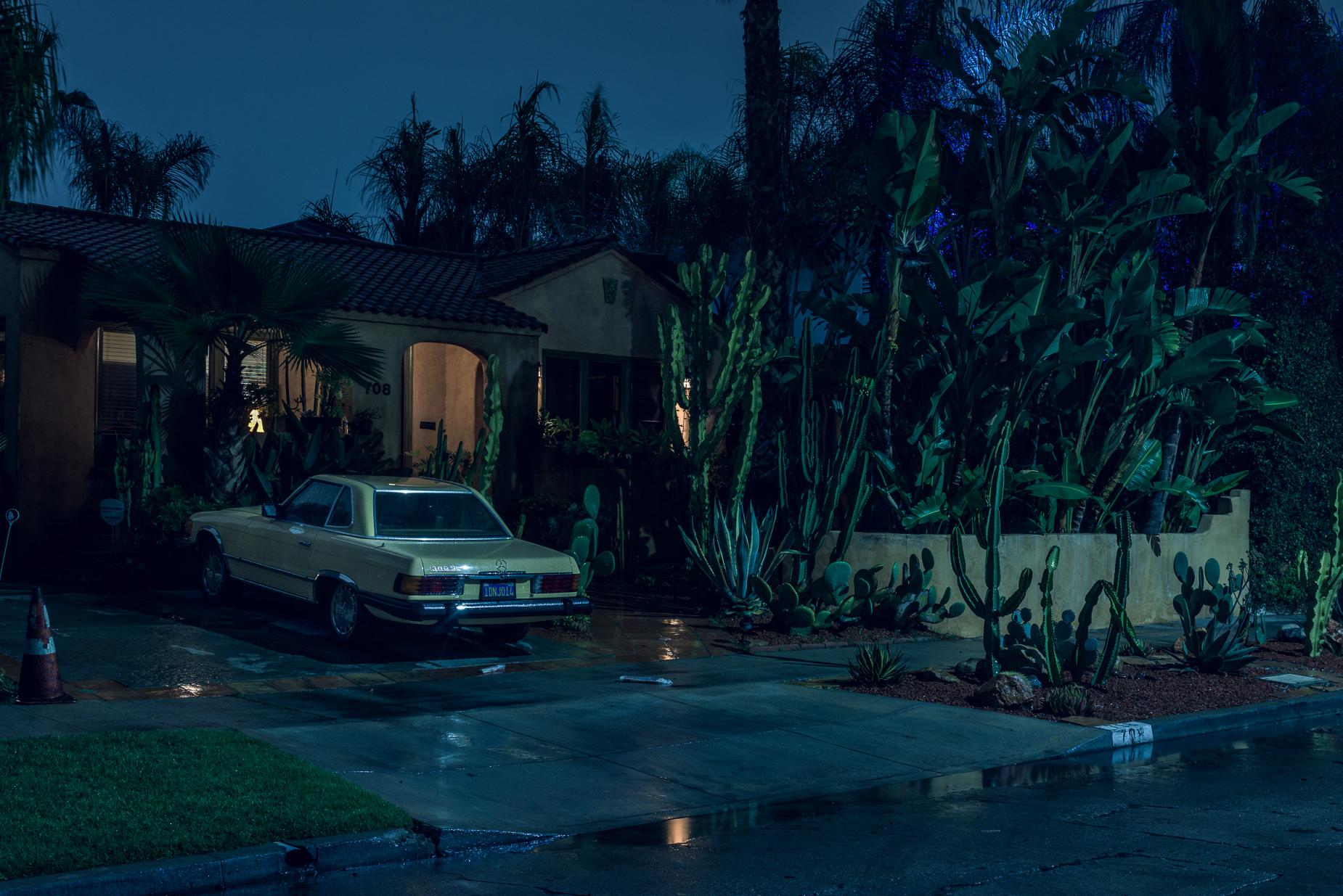 Voiture jaune garée devant une maison individuelle américaine bordée de cactus, de nuit
