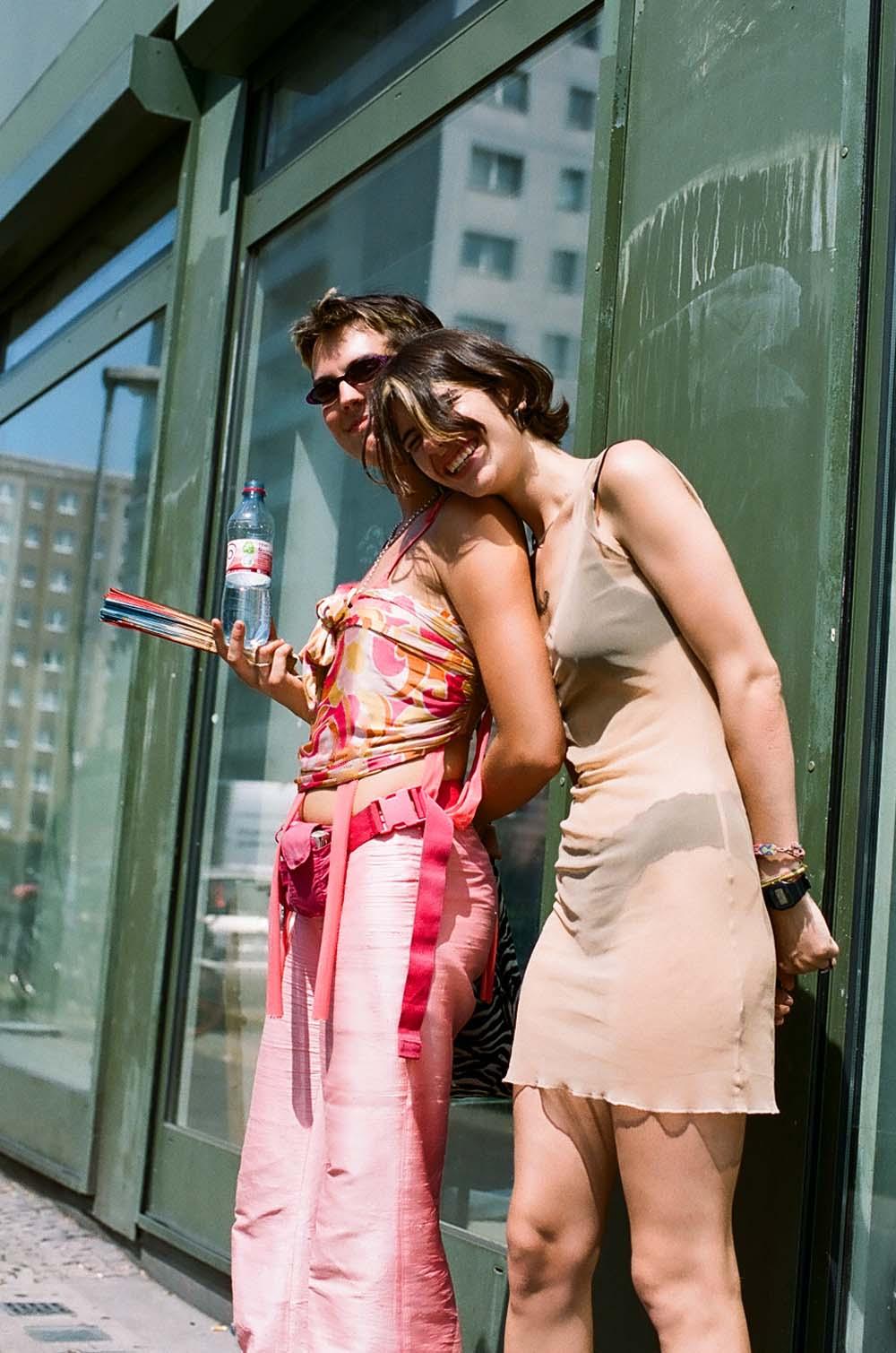 Deux femmes en tenue rose et en robe beige rigolant, tenant une bouteille d'eau devant une vitrine