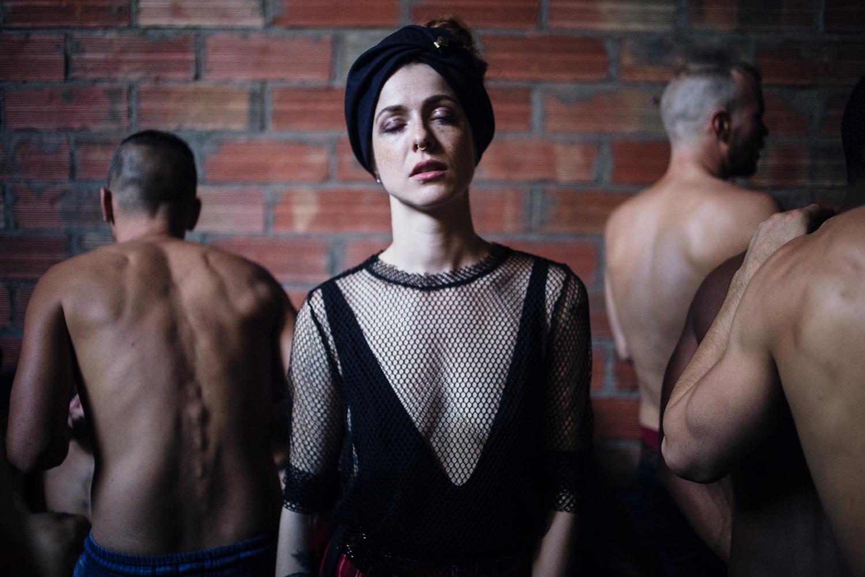 Femme en robe et turban noir statique au milieu de 3 hommes torse nu