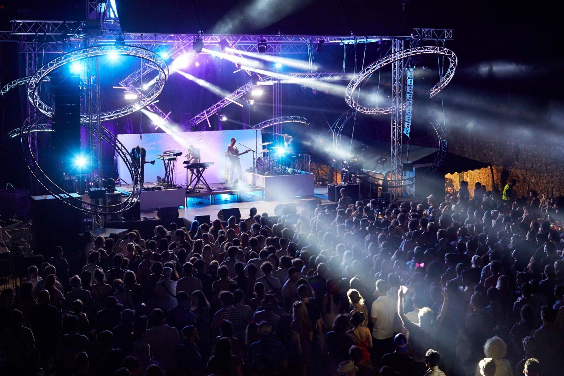 scene sous des lumières bleues avec une foule devant la scene