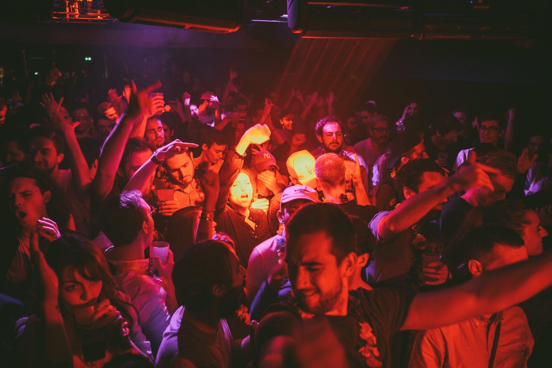 Foule dansant au sacré paris sous une lumière rouge