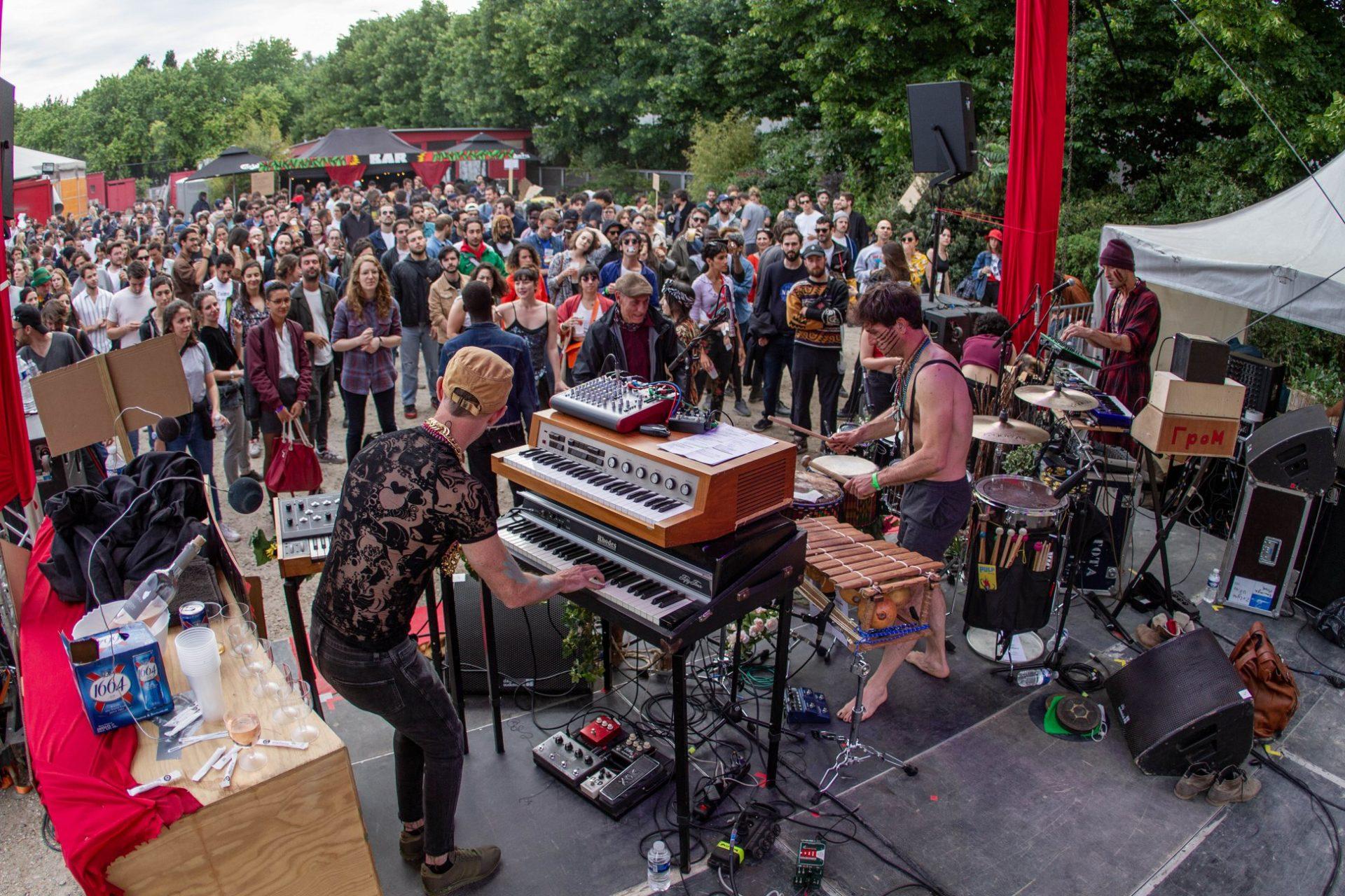 foule devant une scène en openair avec deux pianos sur la scène et 2 musiciens sur scène