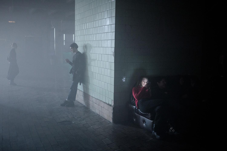 coin de salle enfumée avec 3 personnes regardant leurs téléphones