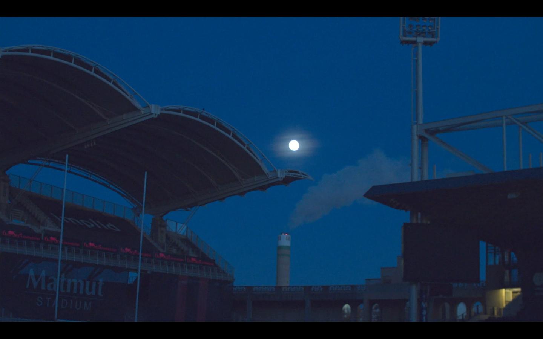 Stade de foot vu de nuit éclairé par le pleine lune