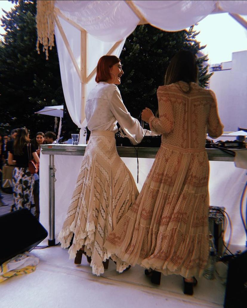 Deux femmes dansant derriere les platines, habillé avec des robes bohemes