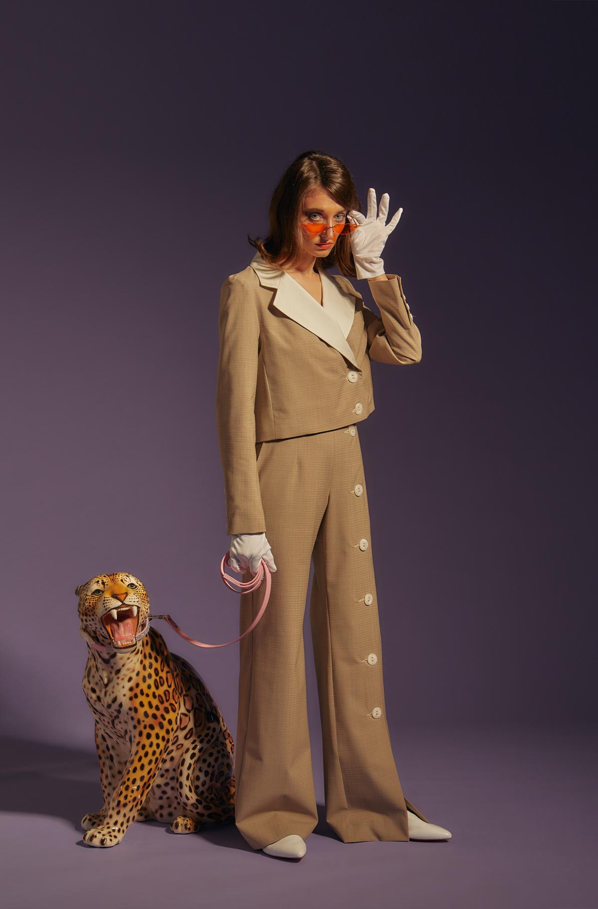 Mannequin Salut beauté en costume beige retro avec des lunettes à verres orange et tenant en laisse une sculpture de guépard