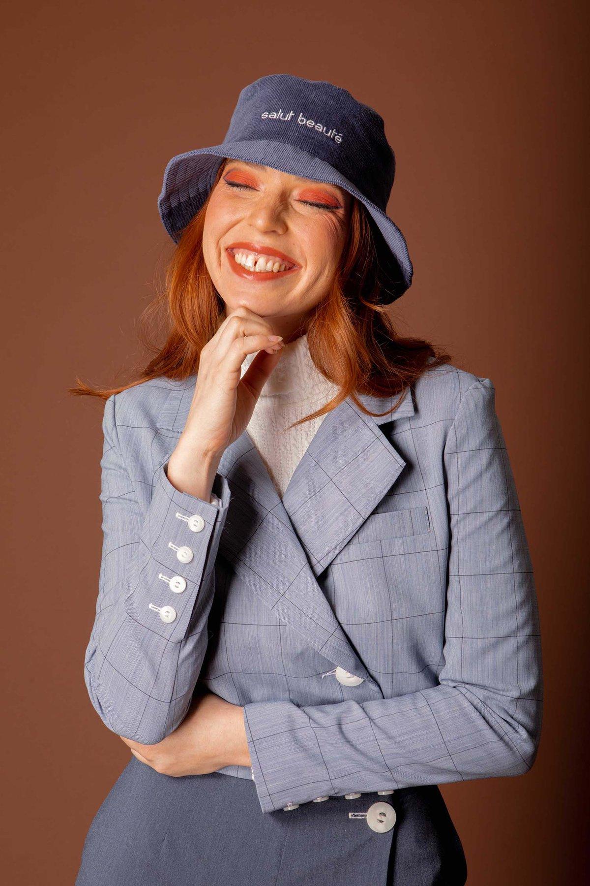 Mannequin rousse Salut Beauté en costume gris avec un bob bleu et un maquillage retro orange