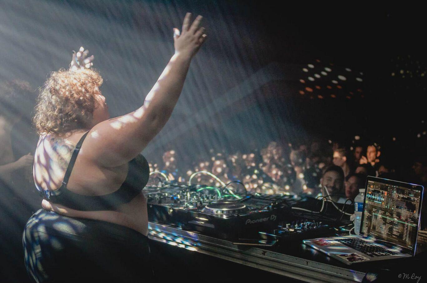Barbara Butch devant ses platines dans une salle avec foule, levant les bras et en soutien george noir