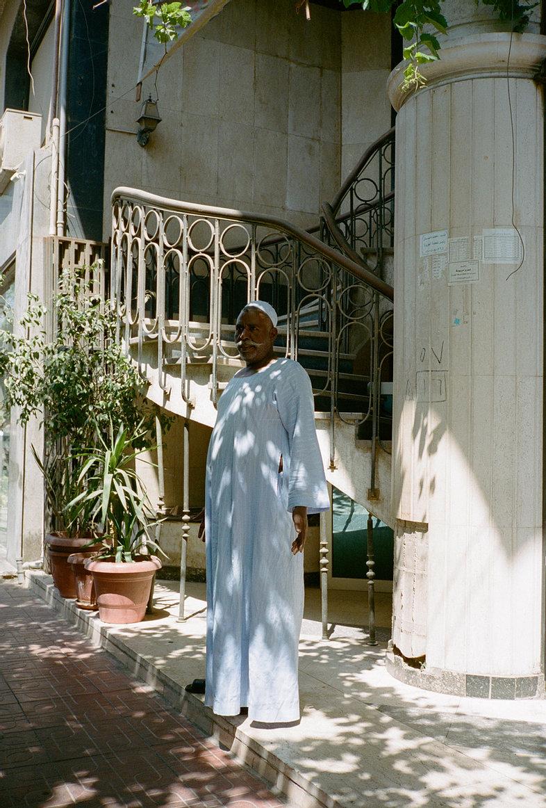 portrait d'un homme agé habillé de blanc posant devant un escalier de fer