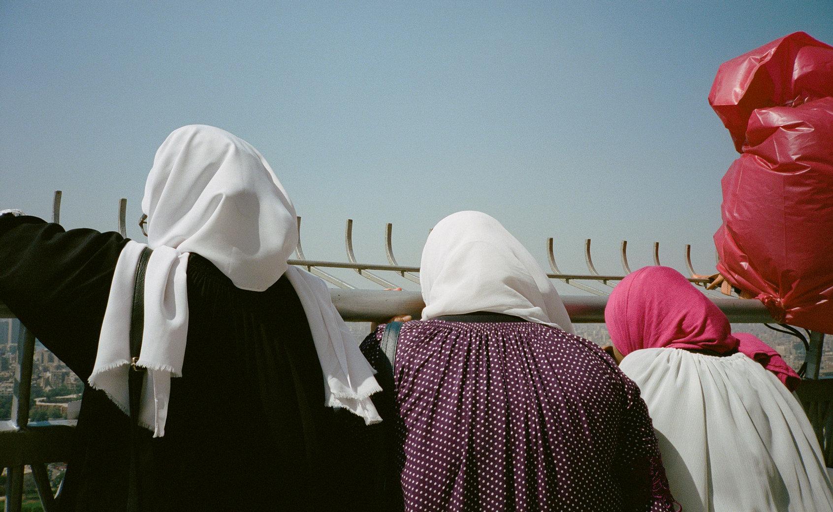 3 femmes voilées photographiées de dos devant une grille