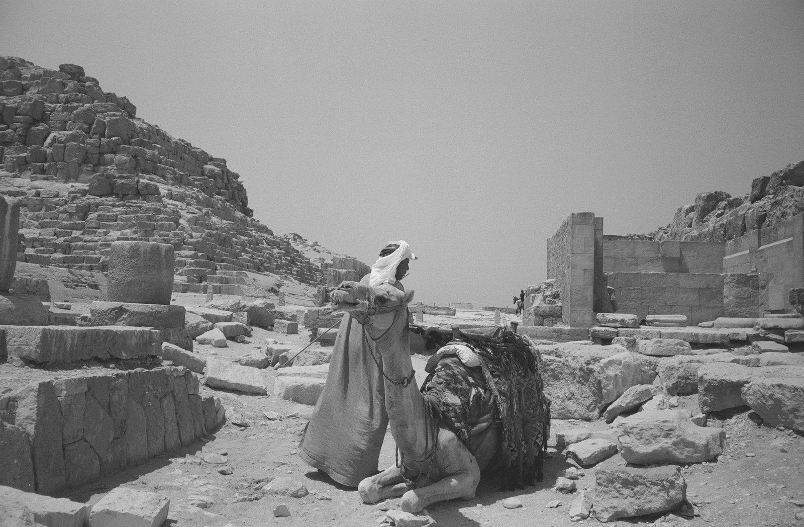 photographie en noir et blanc d'un homme avec son dromadaire au milieu du desert