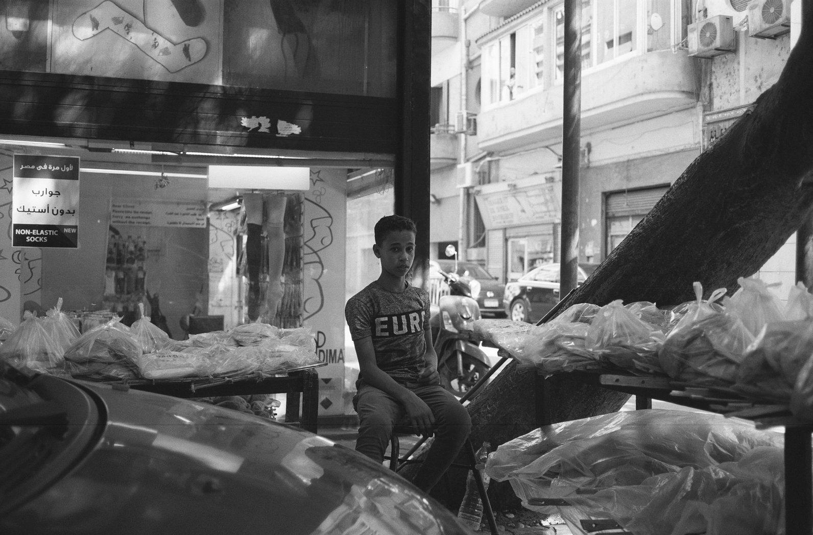 petit garcon assis au milieu d'un marché pris en photo en noir et blanc