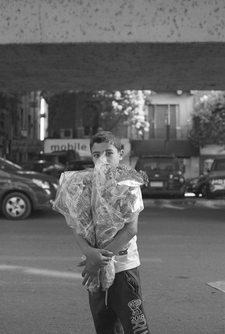 photographie en noir et blanc d'un petit garçon tenant 2 bouquets de fleurs