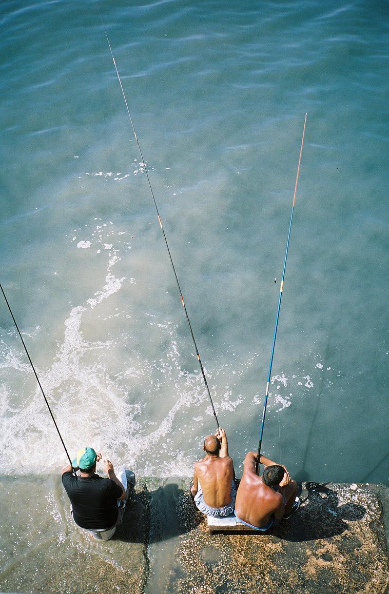 3 hommes avec des cannes en train de pêcher en bord de mer