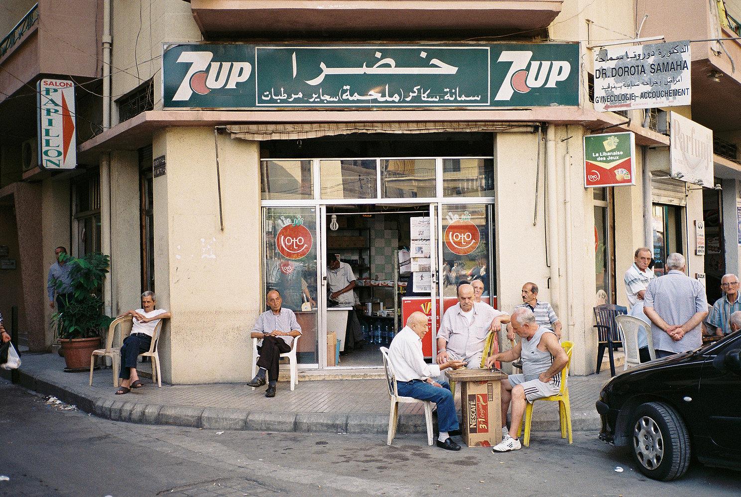 groupe d'homme assis devant un petit commerce