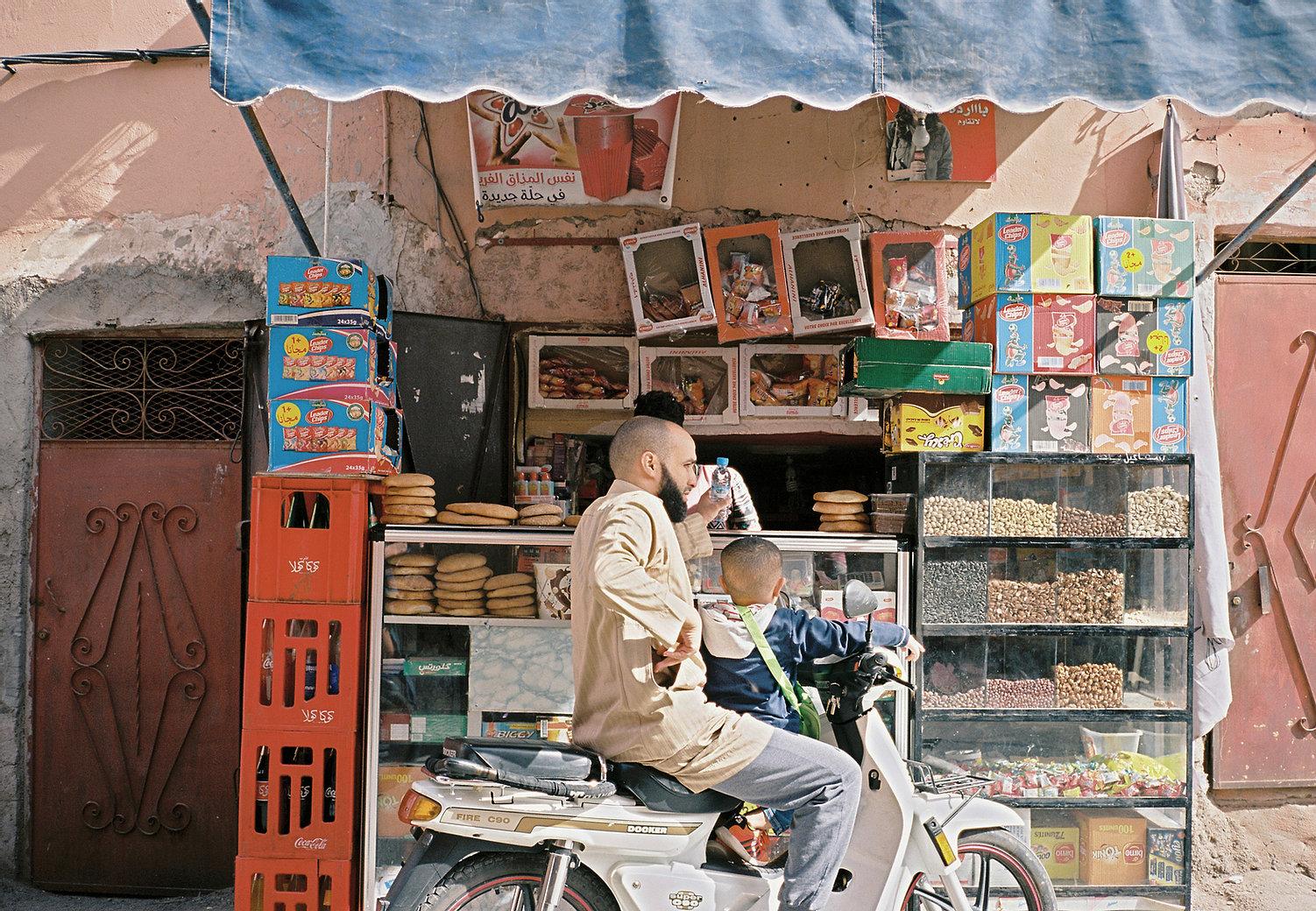 hommes habillé en beige assis suur sa moto avec son fils devant un stand à emporter