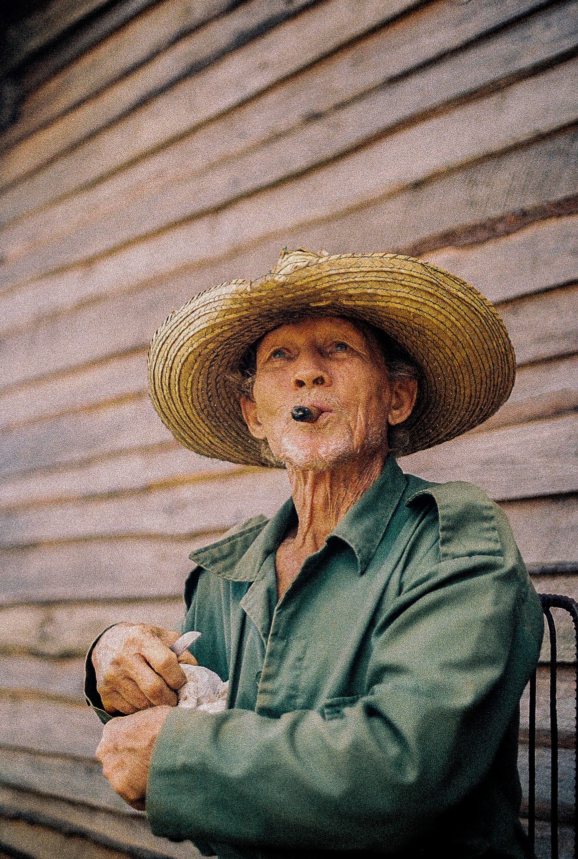 homme agé assis devant une mur de bois, portant un chapeau et fumant un cigare