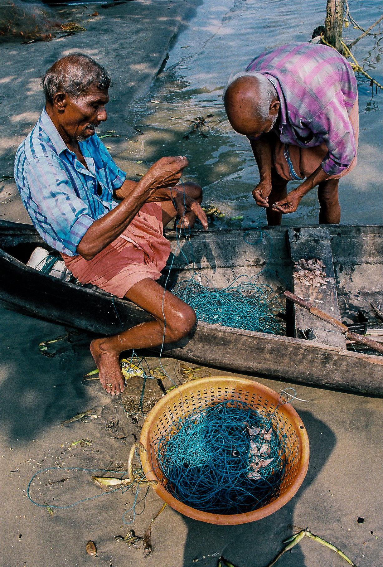 Deux hommes agés autour d'une barque en train de défaire un filet de peche