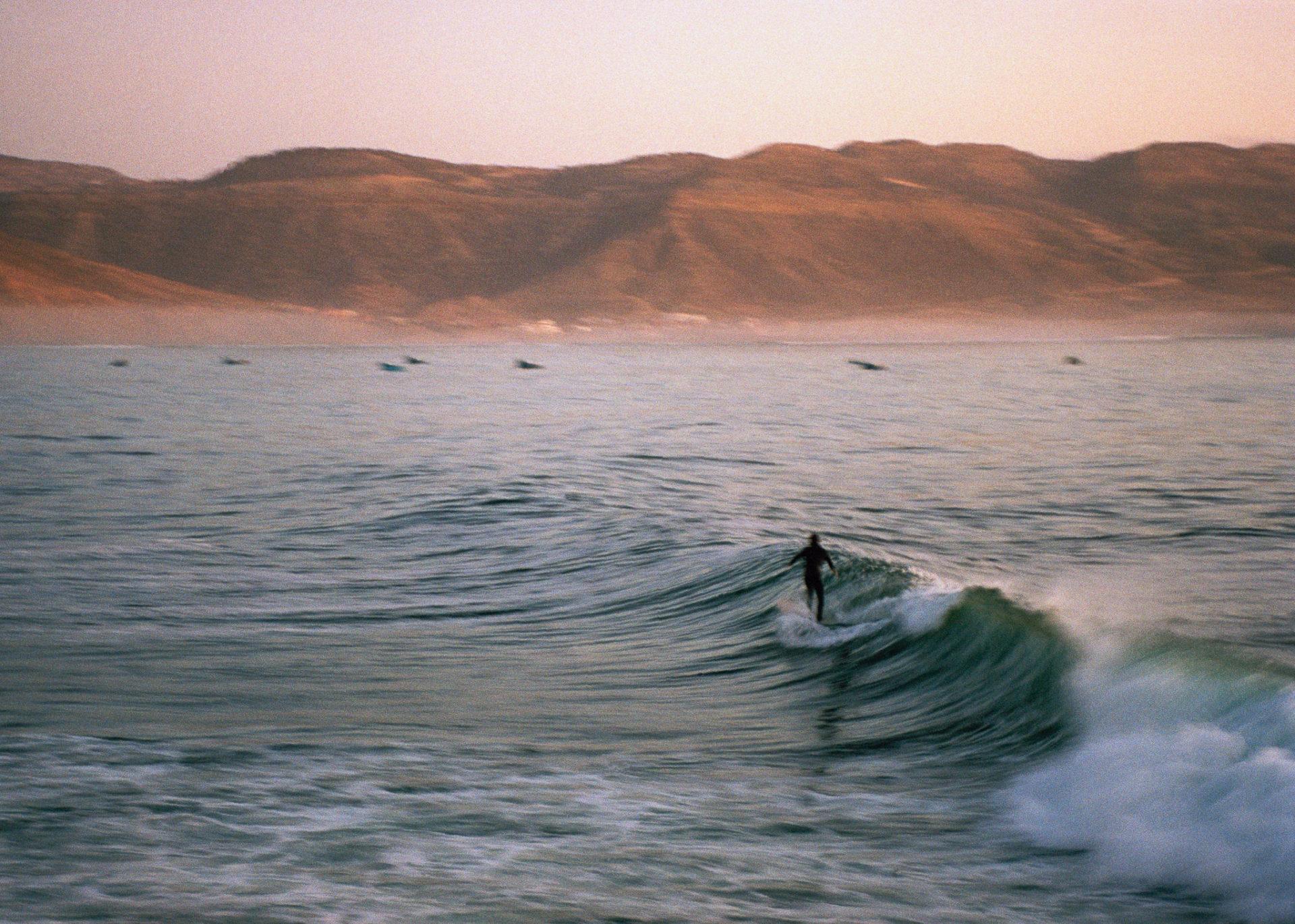 photo d'un côte avec un surfeur sur une vague