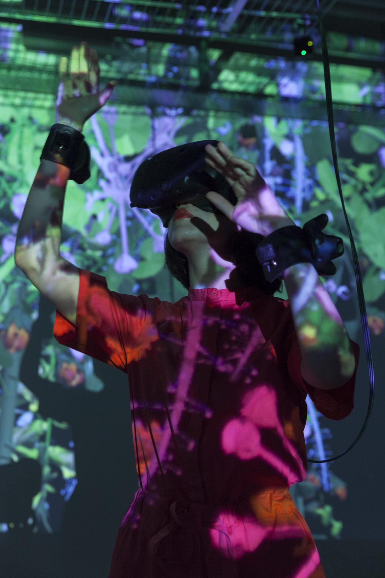 Photo d'une femme portant un casque de realité virtuelle devant une oeuvre de Mélanie Courtinat