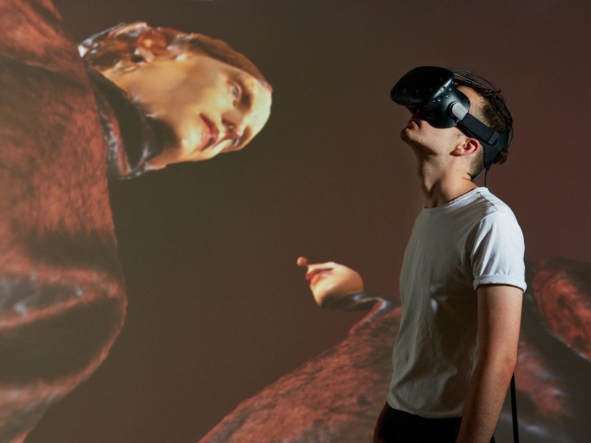 homme avec un casque de VR devant un écran avec des mannequins