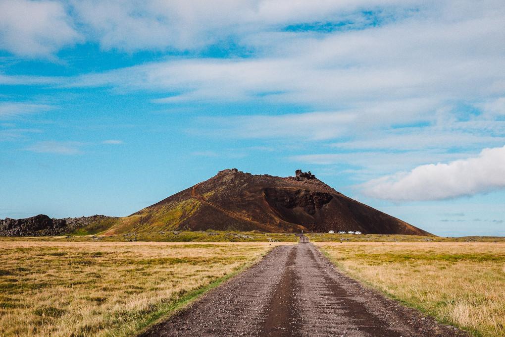 Photographie d'une route menant à une montagne au milieu des plaines islandaises