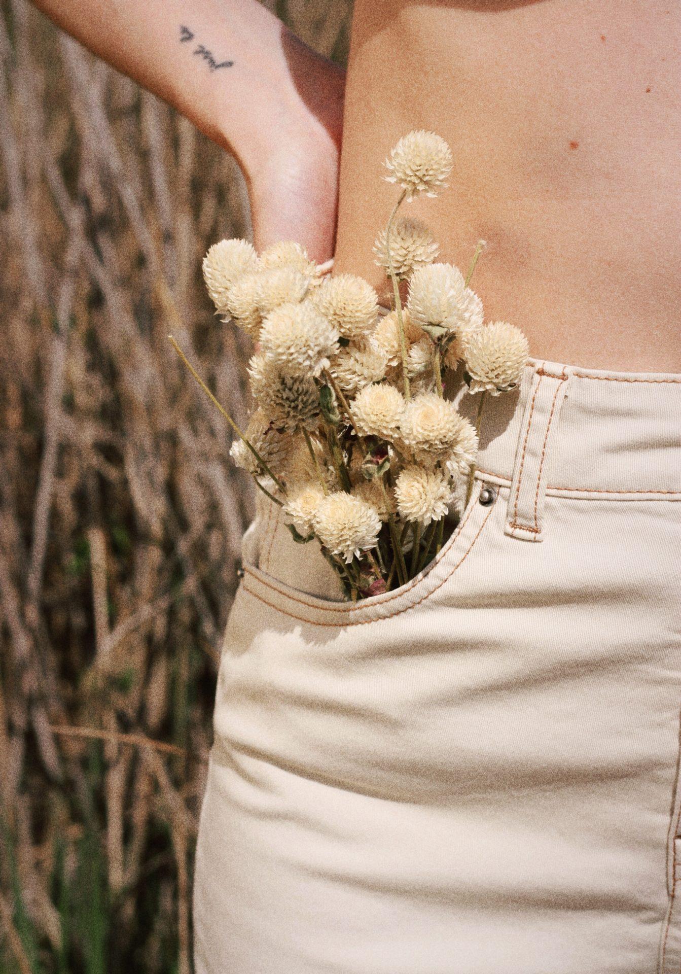 Jean blanc avec un booouquet de fleurs séchées blanches dans la poche