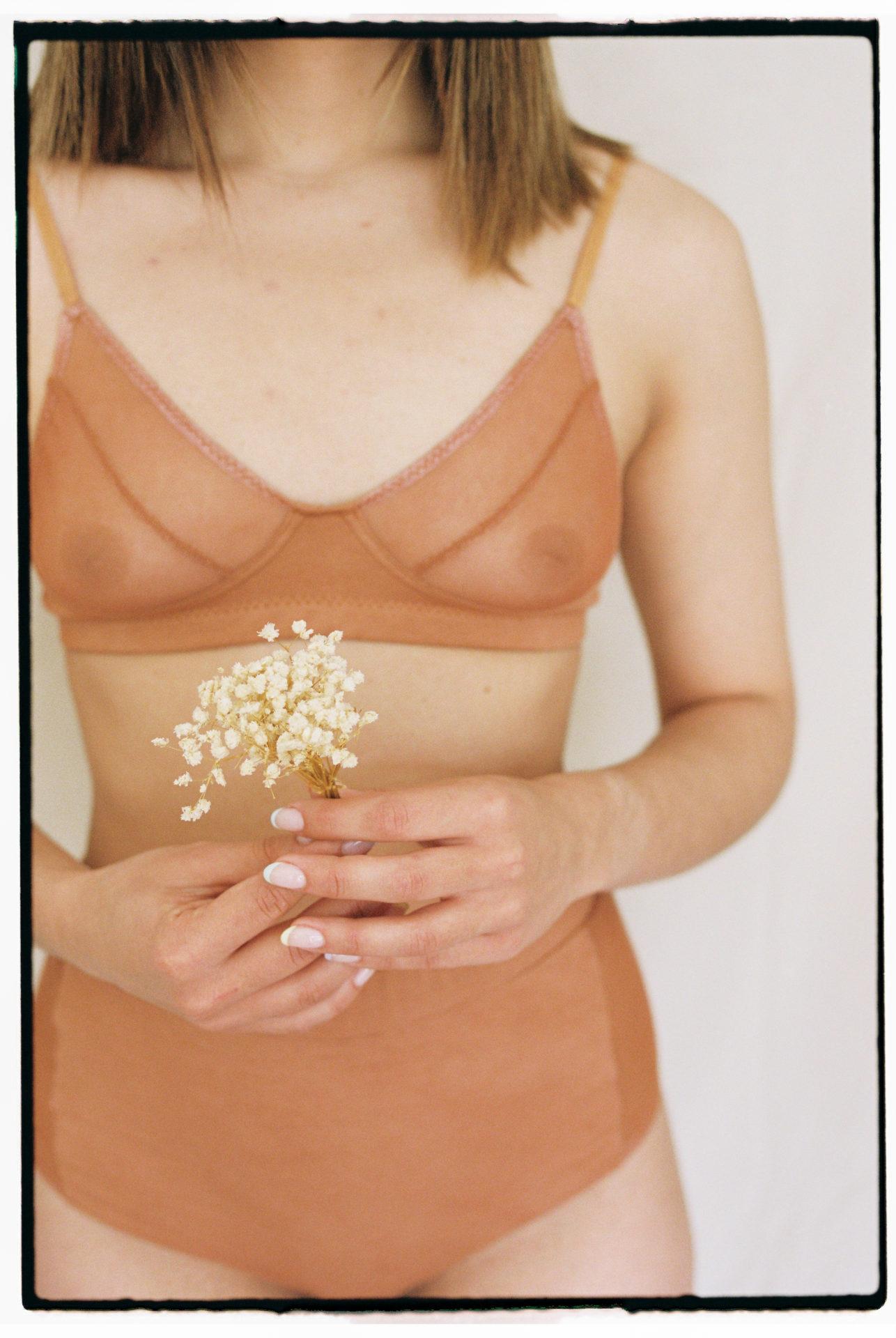 Photo lingerie tons naturels avec une fleur séché blanche