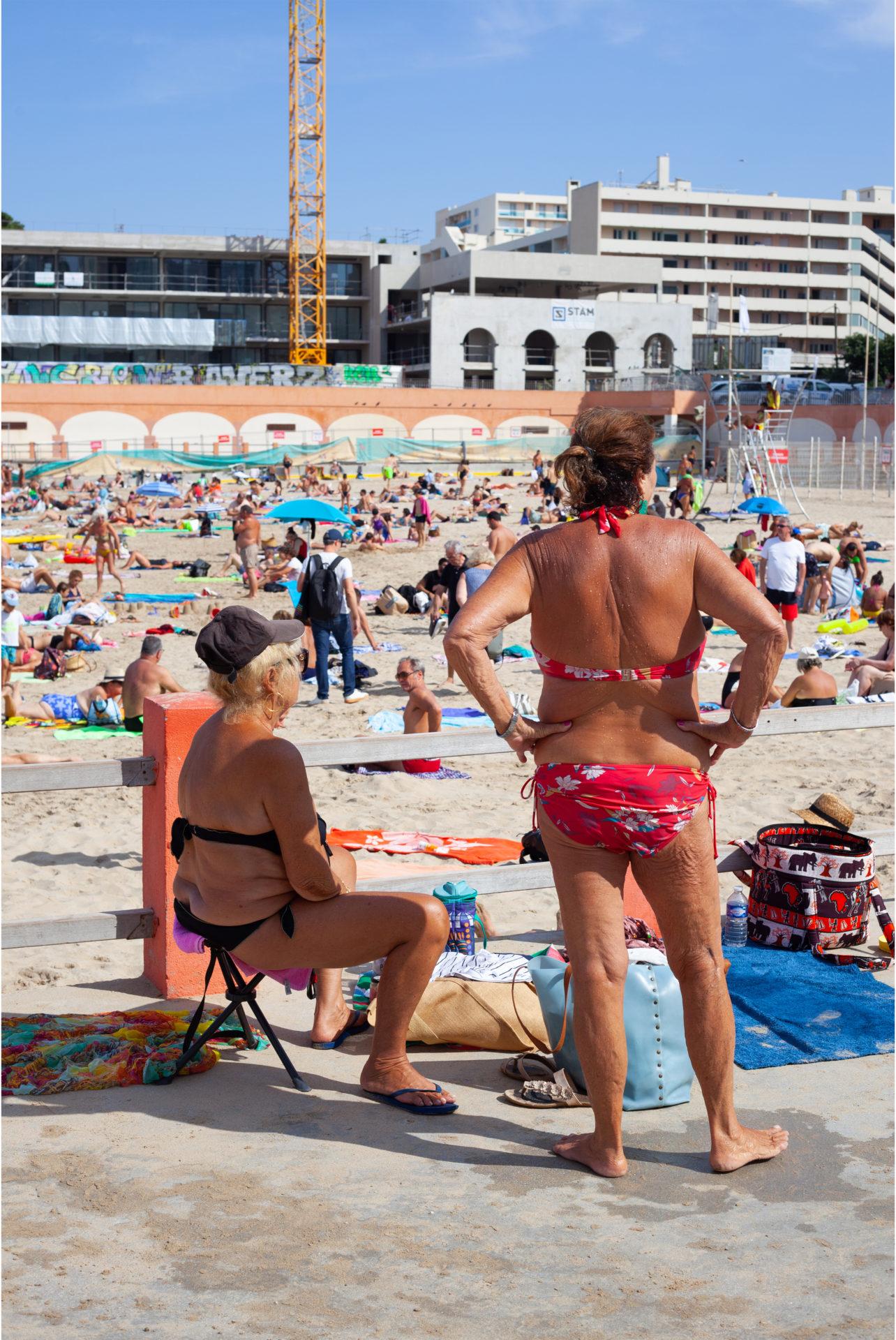 Deux femmes agées en maillot de bain l'une assise et l'autre debout sur la plage