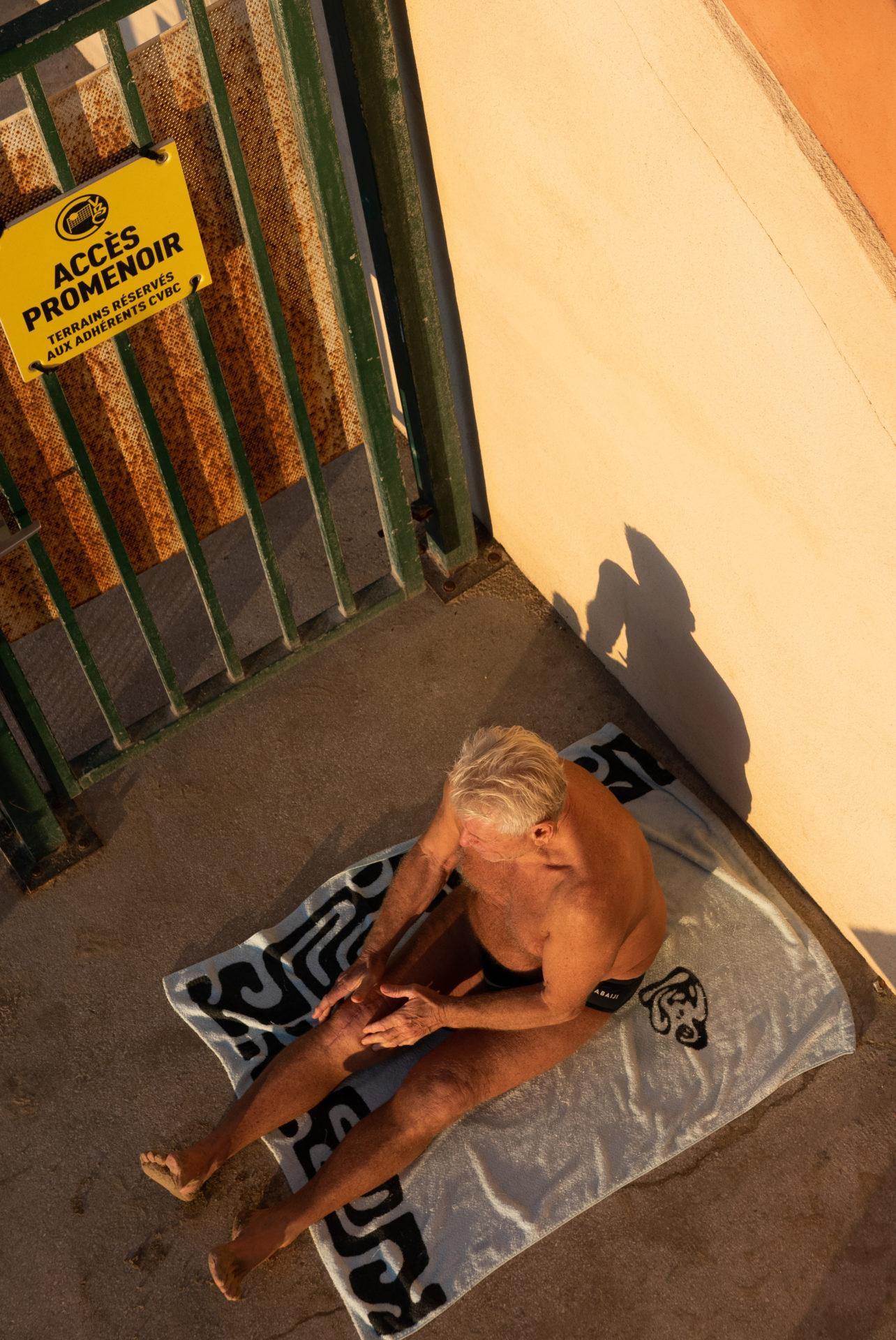 Homme agé en maillot de bain bronzant le long d'une palissade