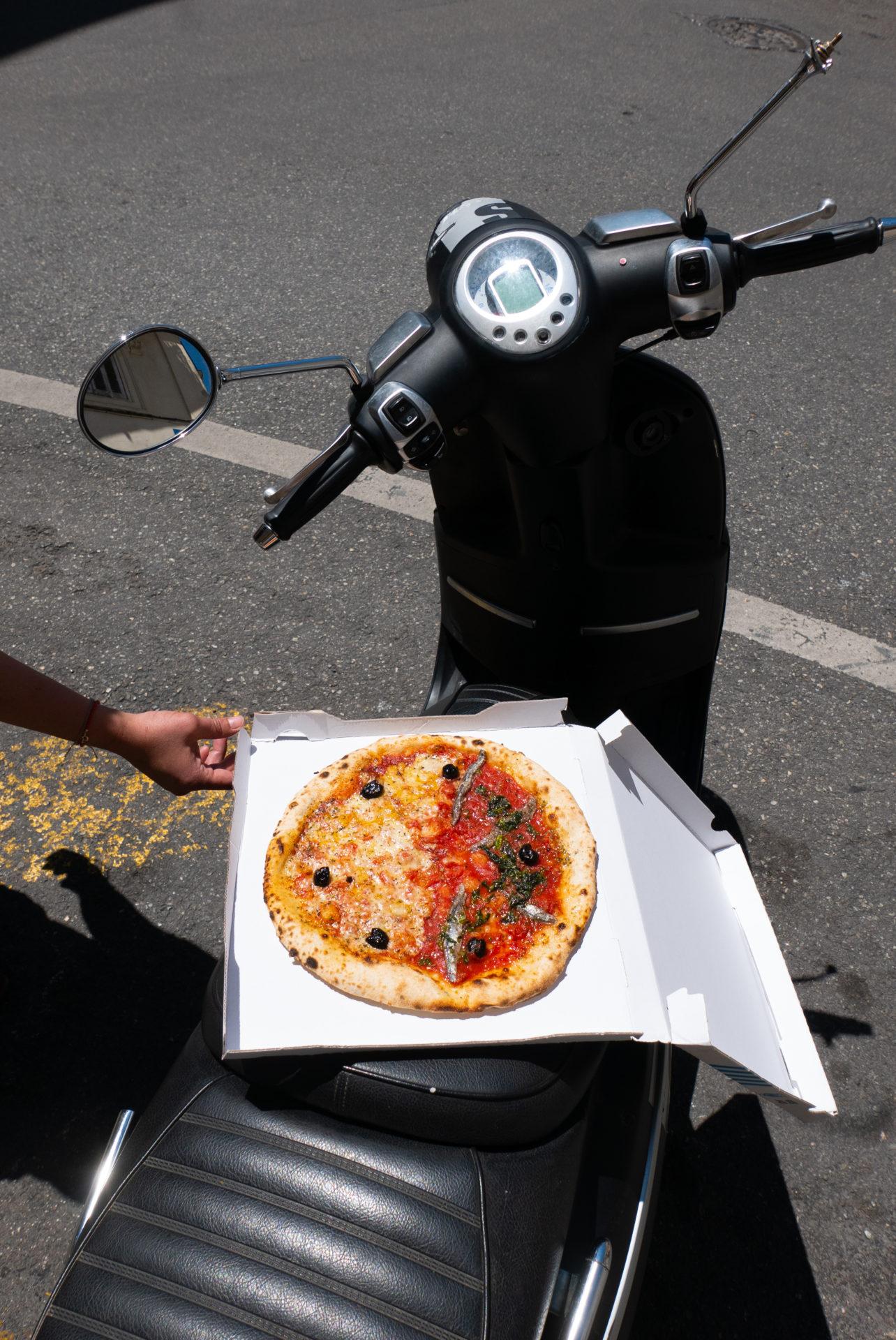 Double pizza dans son carton ouvert sur un scooter noir
