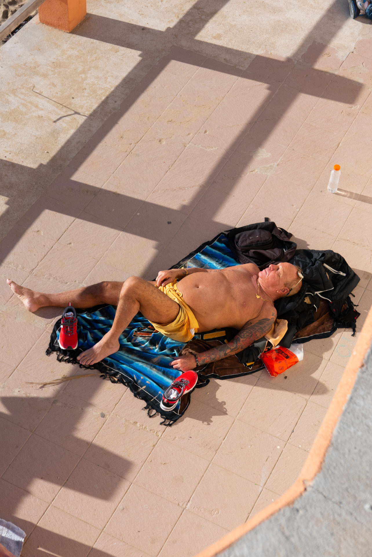 homme en maillot de bain jaune en train. de bronzer le long de la plage des catalans à Marseille