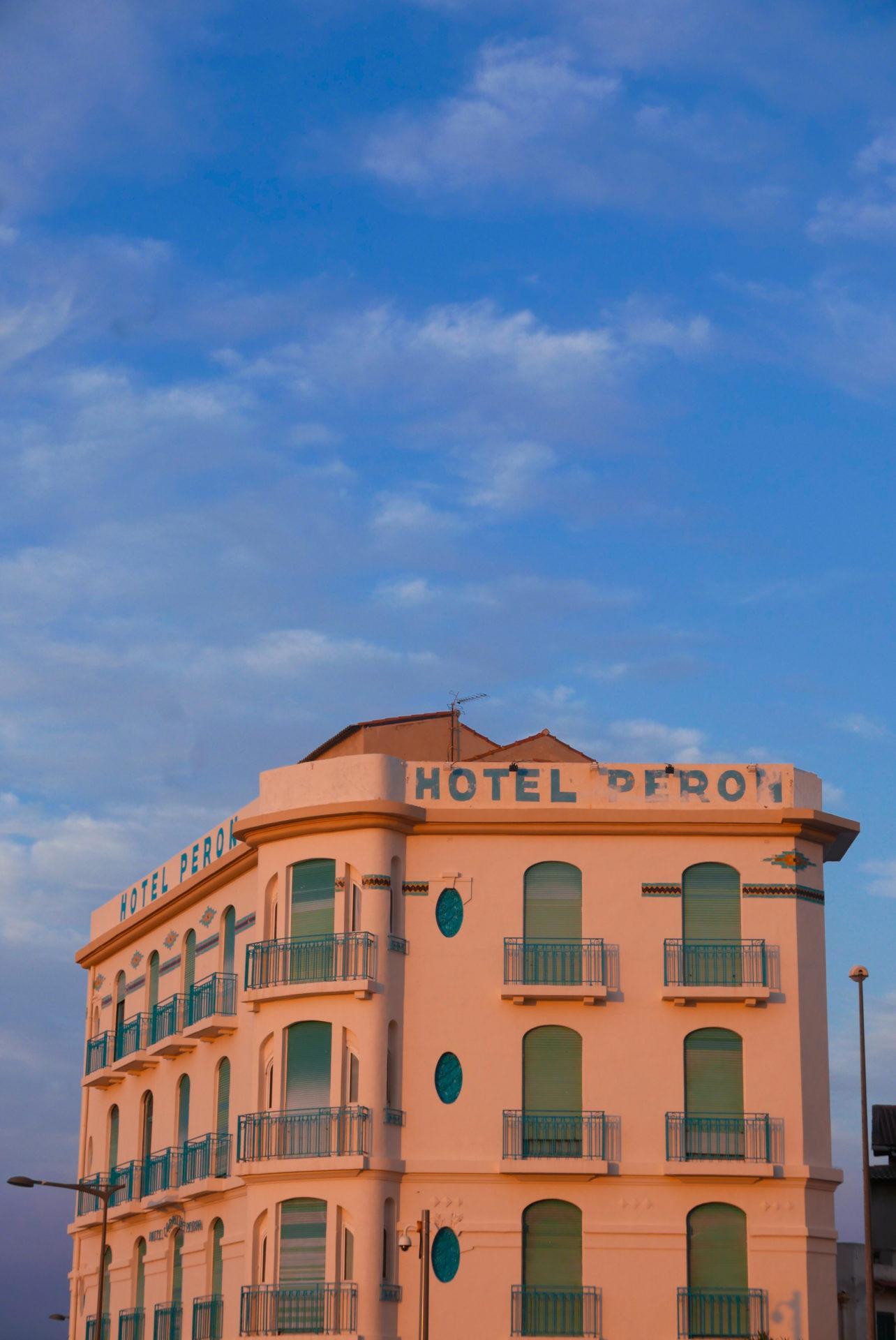 Photo d'un immeuble au teinte de rose sur un ciel bleu