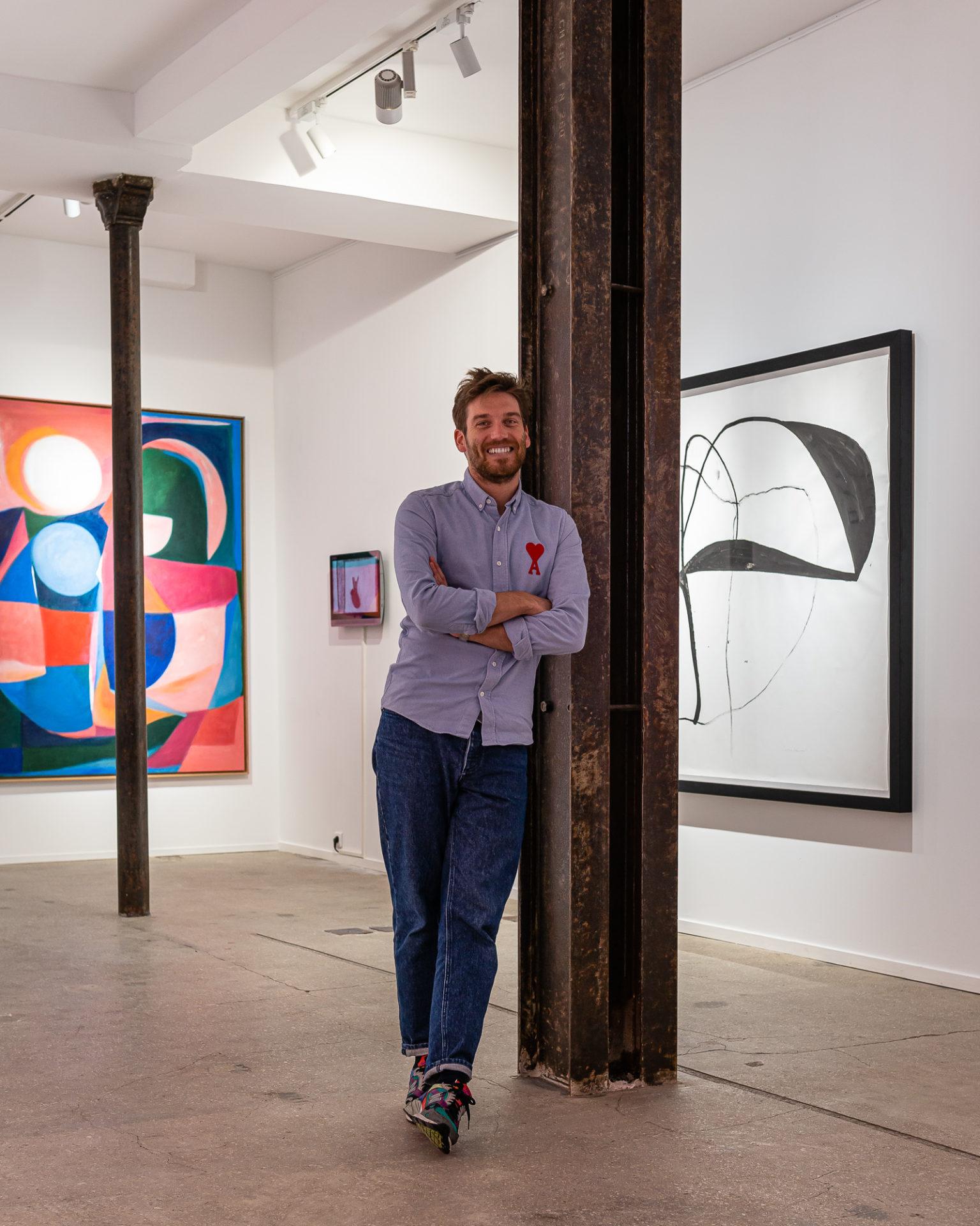 Nicolas Veidig-Favarel fondateur de Double V Gallery en chemise bleu Ami au milieu de sa galerie à marseille